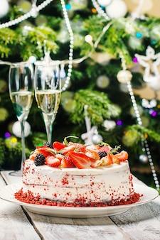 Домашний торт red velvet, украшенный сливками и ягодами на новогоднем фоне