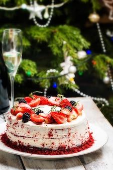 Домашний торт красный бархат, украшенный кремом и ягодами над елкой