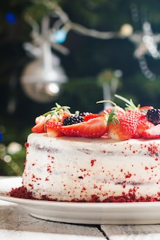 Homemade cake red velvet decorated with cream and berries over christmas surface