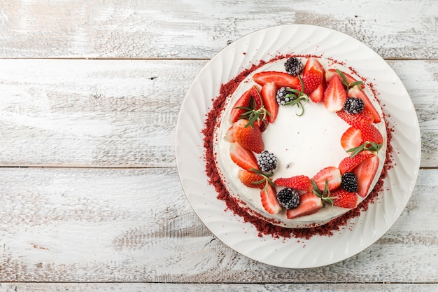 Homemade cake red velvet decorated with cream and berries over white wooden surface, top view