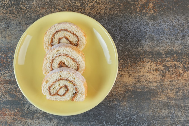 Homemade cake rolls on yellow plate
