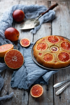 Homemade cake with blood orange on light wooden background.