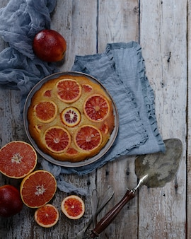 Homemade cake with blood oranges on light wooden table. vintage cake spatula
