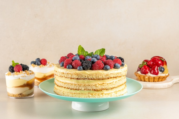 Домашний торт со свежими ягодами и сладкими десертами на столе