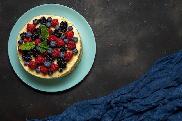Homemade cake with fresh berries on dark background.