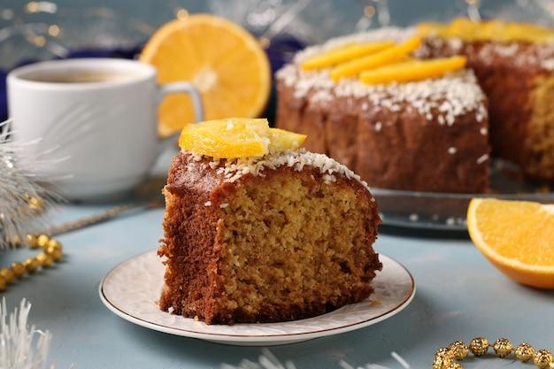 水色の背景と一杯のコーヒーにココナッツフレークをまぶしたオレンジの自家製ケーキ。手前のケーキ。閉じる