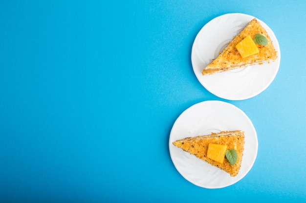 Homemade cake with persimmon and pumpkin on a blue background. top view, copy space.
