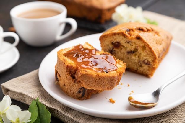 レーズン、アーモンド、ソフトキャラメル、黒いコンクリートの背景とリネンのテキスタイルにコーヒーを入れた自家製ケーキ。側面図、クローズアップ、セレクティブフォーカス。