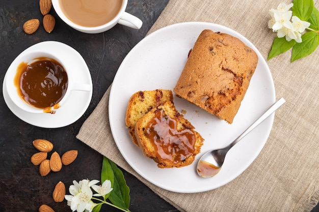 レーズン、アーモンド、ソフトキャラメル、黒いコンクリートの背景とリネンのテキスタイルにコーヒーを入れた自家製ケーキ。上面図、フラットレイ、クローズアップ。