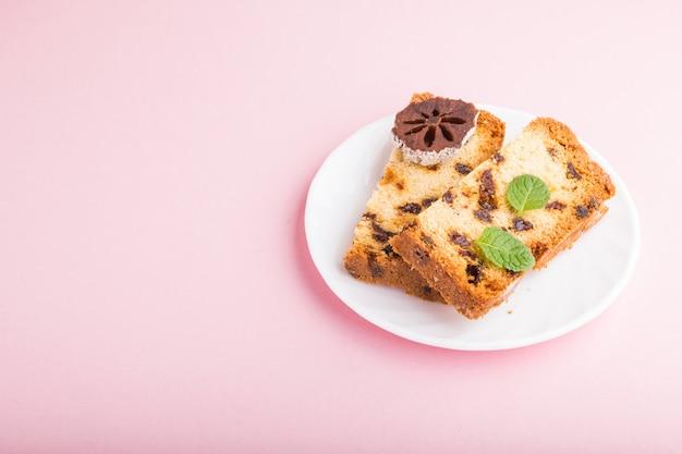 Домашний торт с изюмом и сушеной хурмы на розовом фоне пастельных. вид сбоку, копия пространства.
