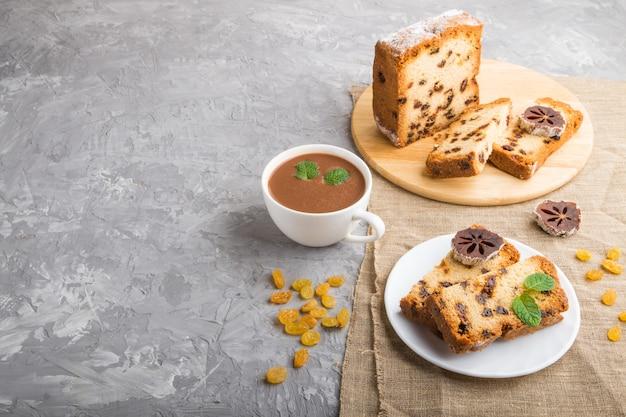 Домашний торт с изюмом, сушеной хурмы и чашкой горячего шоколада на сером фоне бетона. вид сбоку, копия пространства.