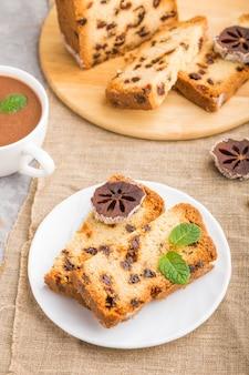 Домашний торт с изюмом, сушеной хурмой и чашкой горячего шоколада на серой бетонной поверхности и льняной ткани