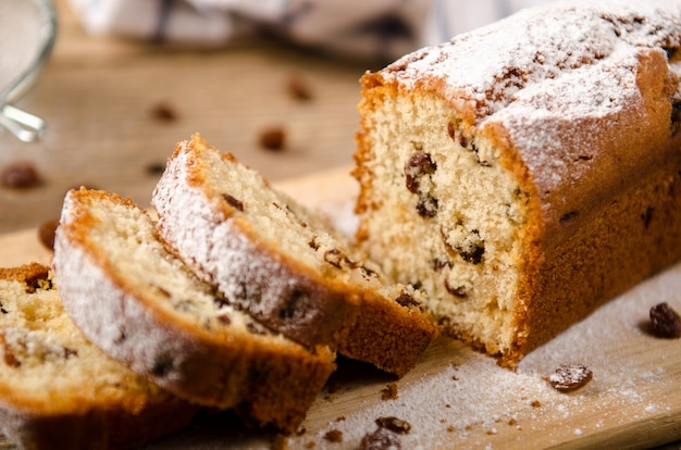 A homemade cake with raisins and powdered sugar is cut on wooden table. white napkin