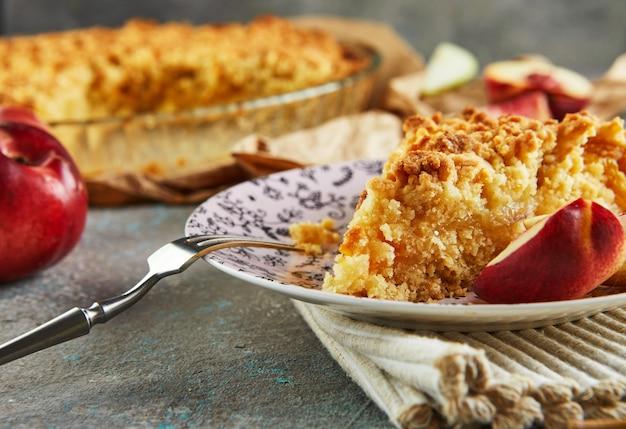 Домашняя выпечка, кусок пирога на тарелке с персиками и грушами на серо-голубом бетоне.