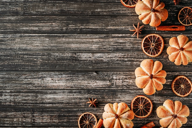 Homemade cakes in shape of pumpkin on dark wooden background, top view with copy space