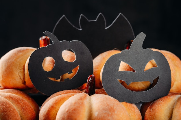 Homemade cakes in shape of pumpkin and halloween decorations on a dark. cooking for halloween
