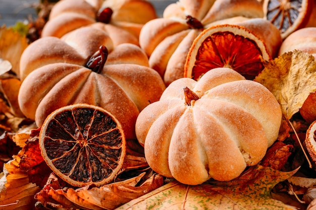 Homemade cakes in the shape of pumpkin with autumn leaves close up. halloween sweets concept