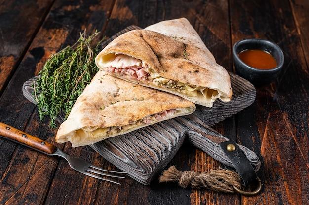 수제 calzone 폐쇄 피자 나무 보드에 햄과 치즈. 어두운 나무 배경입니다. 평면도.