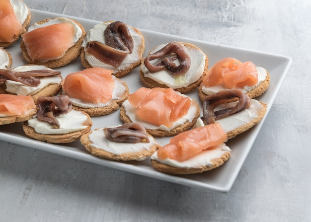 Homemade canapes with smoked salmon, anchovies and cream cheese.