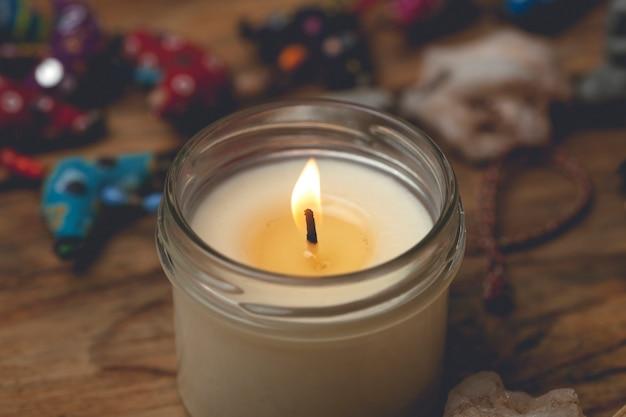 나무 테이블에 유리 촛대에 만든 촛불. 가정의 편안함, 아로마 테라피 및 휴식