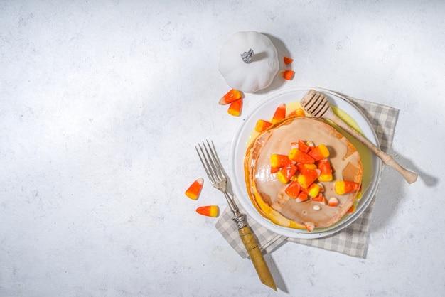 수제 캔디 콘 팬케이크. 달콤한 소스와 전통적인 할로윈 사탕 코드 사탕을 곁들인 노란색과 주황색 팬케이크 스택