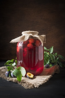Homemade canned plum compote in large jars on wooden board. rustic style.