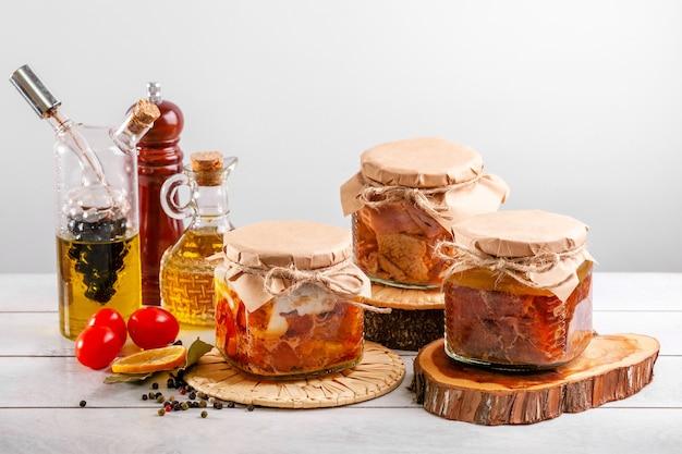 農場の家禽からの自家製缶詰シチュー-ガチョウ、アヒル、鶏肉。缶詰の家禽肉が入ったガラス瓶。