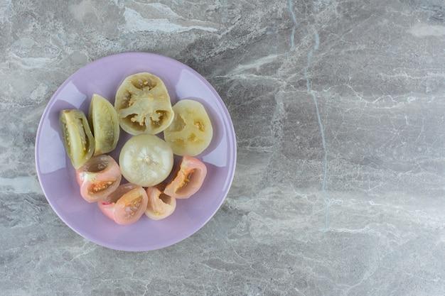 Домашние консервированные ломтики помидоров на фиолетовой тарелке.