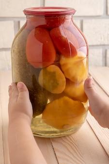 瓶の中の自家製缶詰野菜、子供の手