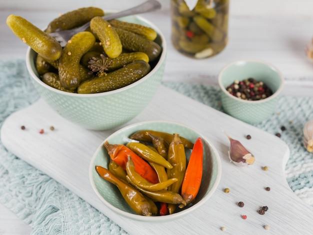Домашнее консервирование. маринованные огурцы-корнишоны и перец с укропом и чесноком в стеклянной банке на белом деревянном столе
