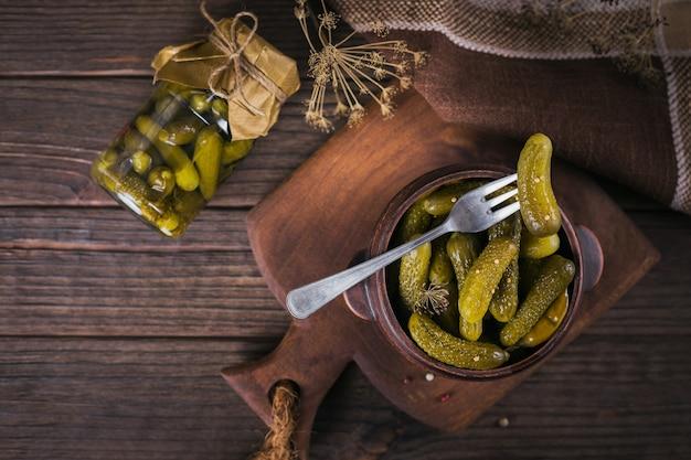 Домашнее консервирование. маринованные огурцы-корнишоны с укропом и чесноком в стеклянной банке на темном деревянном столе. овощные салаты на зиму.