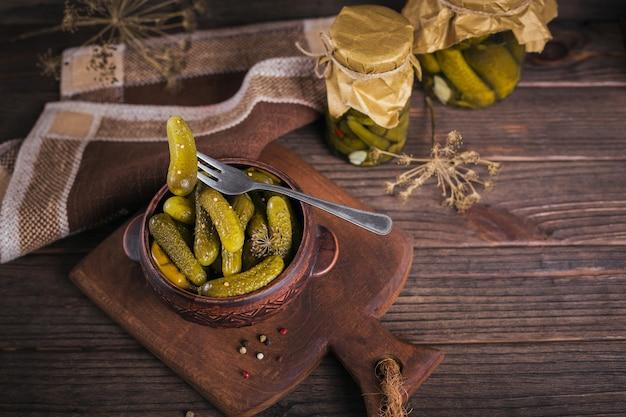 自家製の缶詰。暗い木製のテーブルの上のガラスの瓶にディルとニンニクでマリネしたキュウリのガーキン。冬の野菜サラダ。