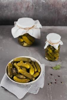 自家製の缶詰。灰色のコンクリートのテーブルの上のガラスの瓶にディルとニンニクでマリネしたキュウリのガーキン。冬の野菜サラダ。