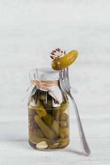 Домашнее консервирование. маринованные огурцы корнишоны с укропом и чесноком в стеклянной банке на белом деревянном столе. овощные салаты на зиму.