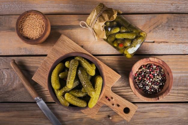自家製の缶詰。木製のテーブルの上のガラスの瓶にディルとニンニクでマリネしたキュウリのガーキン