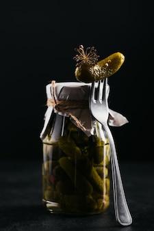 Домашнее консервирование. маринованные огурцы-корнишоны с укропом и чесноком в стеклянной банке на черном