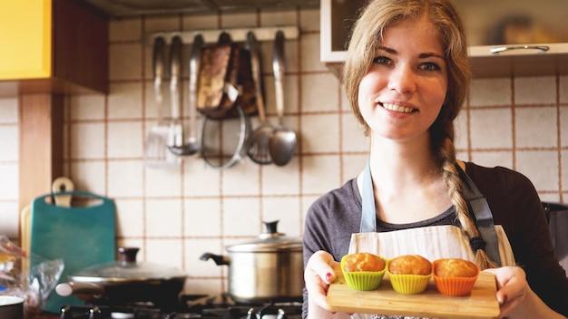 菓子職人の手で焼く皿に自家製キャラメルマフィン。グルメのデザート。セレクティブフォーカス