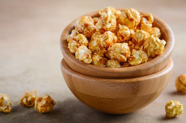 Homemade caramel popcorn in a wooden bowl