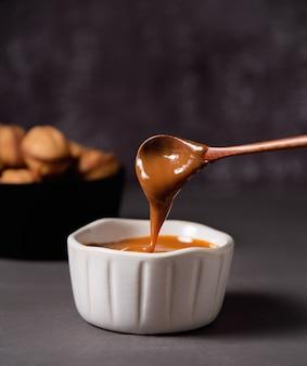 Домашний карамельный соус льется из деревянной ложки в белую миску на темном фоне. вид спереди и крупным планом