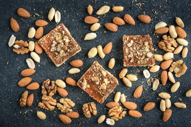 Домашнее карамельное песочное печенье квадраты с орехами положил в форме квадрата на черном фоне с крошками.