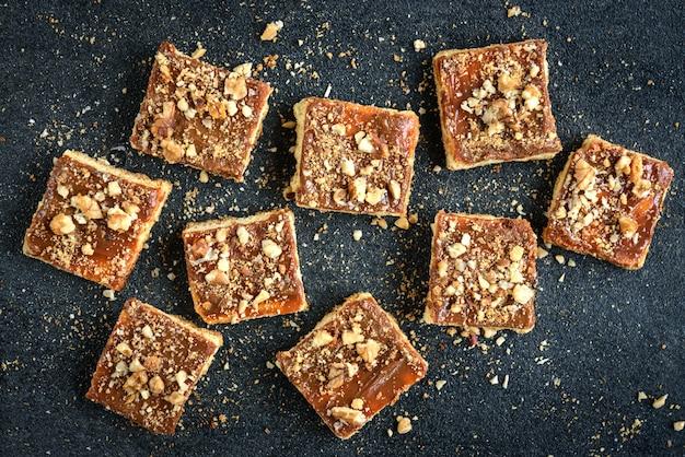 빵 부스러기와 검은 배경에 사각형의 모양에 누워 견과류와 홈 메이드 카라멜 쿠키 광장 쿠키.