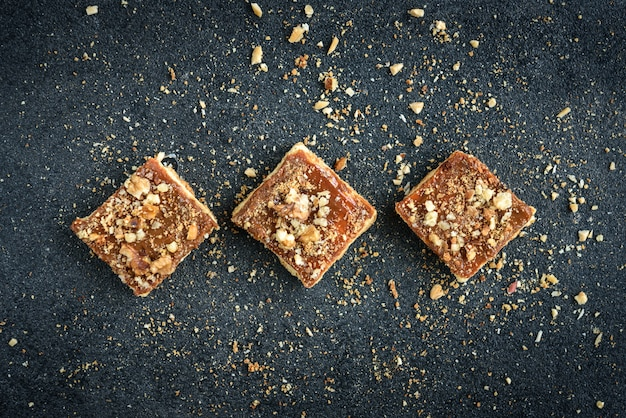 Homemade caramel shortbread squares cookies with nuts laid in the shape of a square on black background with crumbs.