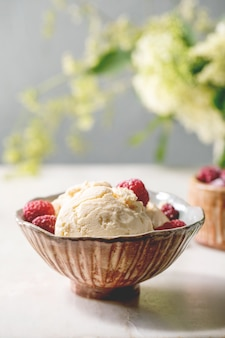 Homemade caramel vanilla ice cream with frozen raspberries in ceramic bowl standing on white marble table with flowers behind.