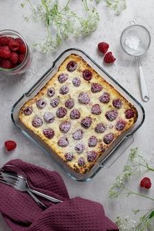 カッテージチーズ、セモリナ粉、ラズベリーを添えた自家製キャセロール、粉砂糖を添えた甘いケーキ。