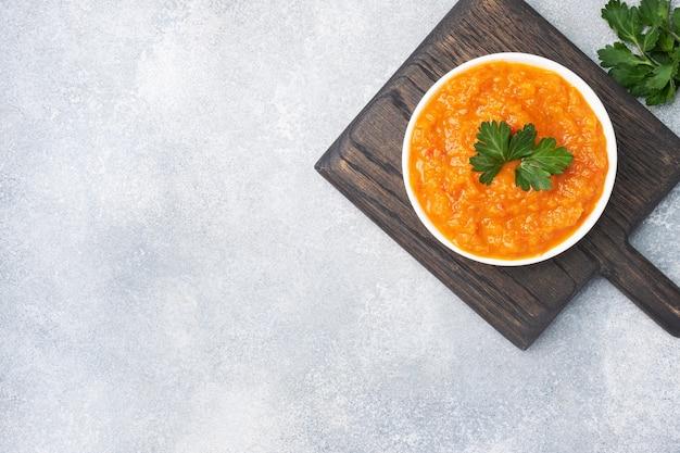 灰色の背景に、セラミックプレートのズッキーニトマトと玉ねぎから自家製キャビア。自家製の缶詰、野菜の煮込み缶詰。上面図、コピースペース