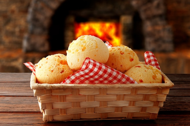 Homemade cheese bread, traditional brazilian snack, in the basket after leaving the oven on a rustic kitchen table