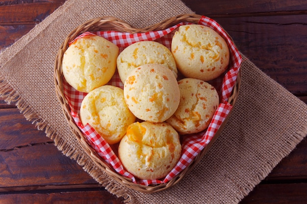 Homemade cheese bread, traditional brazilian snack, in a heart-shaped basket on a rustic kitchen table