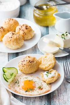 Homemade cheese buns with flax seeds, fried egg, honey and butter