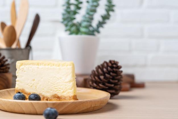 自家製チーズケーキまたはバターケーキを木の皿またはブルーベリーと一緒に皿に置き、テーブルの上に置きます。