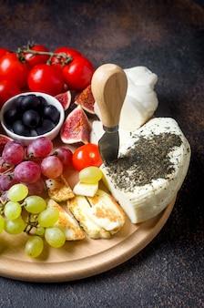 나무 보드에 민트와 함께 halloumi 튀김을위한 수제 치즈. 토마토 고추, 올리브, 포도, 무화과, 허브와 함께 어두운 배경에 전통적인 그리스 또는 키프로스 치즈